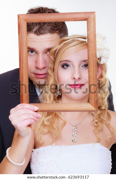 Wedding day, positive relationship concept. Groom and bride holding, posing with empty photo frame
