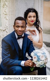 Wedding day. Stylish african groom and his pretty bride. African wedding couple emotional portrait loving bride and groom.