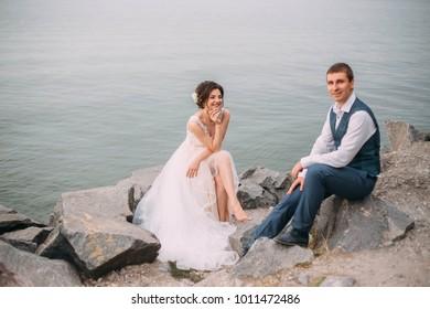 Wedding day. Stylish young couple walking on a background of wildlife at sunset. Fine's Photo