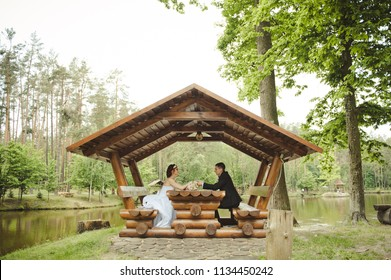 Wedding day in summer.The bride and groom are sitting in a wooden gazebo. Couple in love posing sitting on wooden bench in gazebo.