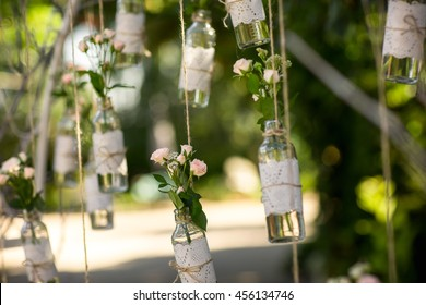 Wedding decor, bottles with flowers on green background