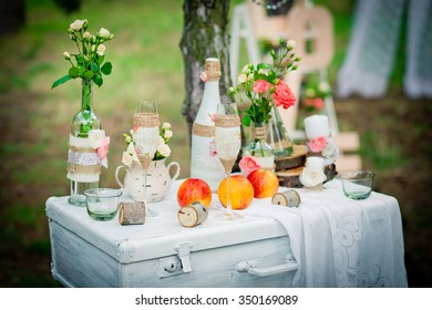 Wedding decor with bottles, glasses, roses, vases and peaches on a ancient suitcase. Decoration of a wedding photoshoot.  Details of a wedding decor.