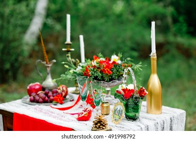 Wedding decor with fruit, flowers, candles  on a table in style of a boho-chic. Decoration of a wedding photoshoot.  Details of a wedding decor.