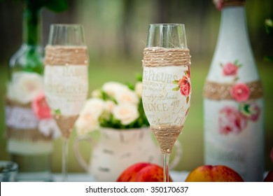 Wedding decor with wedding glasses in style of a shabby chic, bottles, peaches. Decoration of a wedding photoshoot.  Details of a wedding decor.