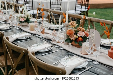 Wedding decor for guests at banquet, dried flowers, floristry and candles, boho style, service for marriage ceremony. Bright bouquet, dishes and cutlery, glasses on table and chairs on green lawn