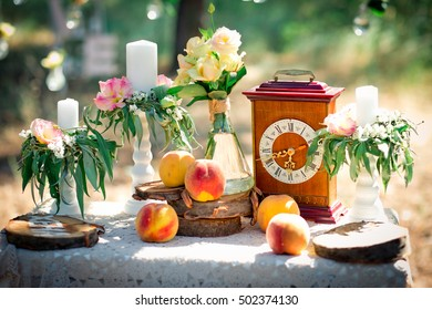 Wedding decor for photographing with the bracket clock, flowers, candles and peaches on a ancient suitcase. Roses in bulbs on a background . Decoration of a wedding photoshoot.