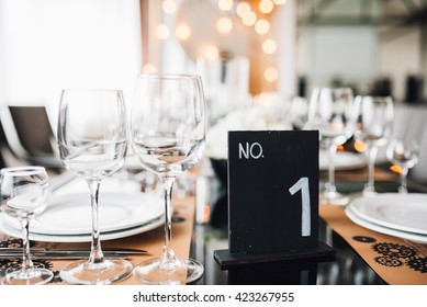 Wedding decor. Reception. Table number 1 on black wooden stand. Glasses and cutlery on side. Steampunk style