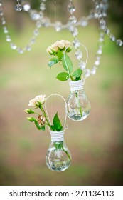 Wedding decor with wedding rings and roses in bulbs. Decoration of a wedding photoshoot.