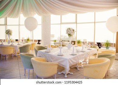 Wedding decor. Wedding tables in restaurant with white flowers and huge white balloons