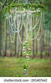 Wedding decor with wheel, glass beads and roses in bulbs as vases. Decoration of a wedding photoshoot.