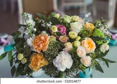 Wedding decoration. Bouquet of white and peach flowers on a table near a candle turquoise. Close-up.
