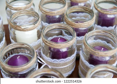 Wedding decoration - candles in glass jars decorated with lace, sackcloth and ribbons over wooden table - high angle
