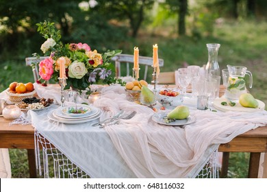 wedding, decoration, celebration, floral design, holidays concept - romantic table setting with white tablecloth, plates, crystal goblets, beautiful bouquet of roses and peonies and candels