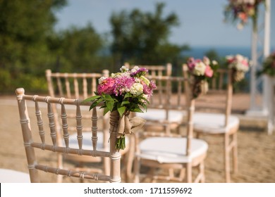Wedding decoration - ceremony setup chairs with flowers by the sea