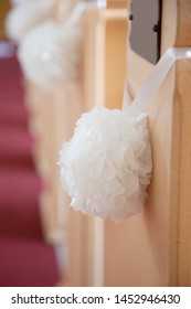 Wedding decoration in a church with a white hanging ball of flowers hung by a ribbon and blank pew plaque