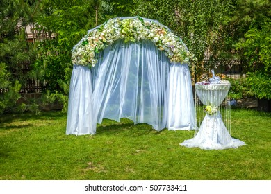 Wedding decoration. Flowered arch and table covered with white chiffon prepared for the wedding ceremony in the green garden.