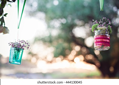 Wedding decoration of glas bottles with flowers hanging