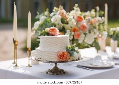 Wedding decoration table in the garden, floral arrangement, In the style vintage on outdoor.  Wedding cake with flowers. Decorated table with flowers, served for two people.