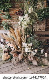 Wedding decorations. The wedding ceremony area in the loft against a brick wall is decorated with compositions of flowers and greenery, candles and dried flowers