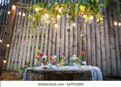 Wedding decorations. Flowers, lights, lighting bulbs, wooden wall, unusual place for marriage.