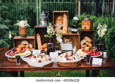 Wedding decorations. Reception. Buffet. Fruits and cheese on plates with bread in boxes. Food bar decorated by flowers and lanters