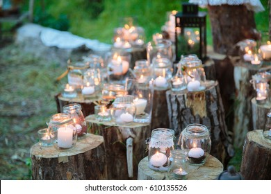Wedding decorations in rustic style. Outing ceremony. Wedding in nature.  Candles in decorated jars