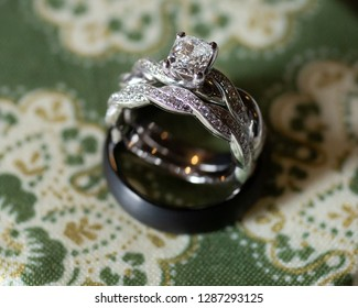 Wedding detail close up. Brides twisted white gold and diamond wedding and engagement ring and grooms black titanium wedding band on green pattered fabric.