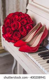 wedding details: bouquet of red roses flowers and bride's shoes stand on classic white piano