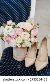 Wedding details. On the chair are flowers and wedding shoes, next to the rings