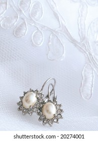 Wedding details. silver ear-rings with pearls lying on embroidered veil