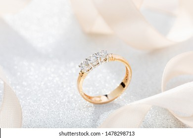 Wedding diamond ring on glossy background with beige ribbon. Rose gold engagement or proposal ring with gemstone