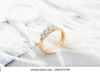 Wedding diamond ring on glossy background with white feathers. Rose gold engagement or proposal ring with gemstone