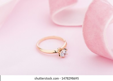 Wedding diamond ring on pastel background with pink ribbon. Gold engagement ring with gemstone. Proposal ring still life