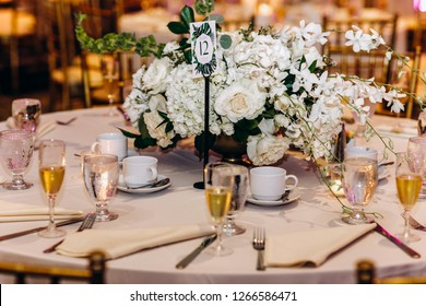 Wedding dinner table decor. Indian reception or banquet. Pastel and white colors. Long tables decorated with white flowers and golden cutlery.