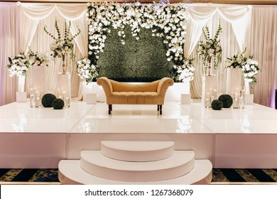 Wedding dinner table decor. Indian reception or banquet. Pastel and white colors. Beiege sofa for Hindu newlyweds. Burning candles as a centerpiece