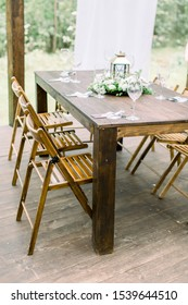 Wedding dinner table decoration outdoors in forest. Wooden table setup for wedding party or dinner reception. Rustic decorations on the table