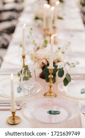 Wedding dinner table at reception. Beautiful white delicate candles burn in metal candlesticks, against background of white and pink tablecloth, flower arrangements and glass plates with gold beads