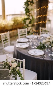 Wedding dinner table reception. Beautiful decoration on a chair made of rose flowers. Chiavari Chair, Tiffany. Against background of a round table with table setting and bokeh from a garland on a tree