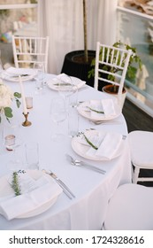 Wedding dinner table reception. Close-up of a round wedding table with white plates and a menu enclosed in a napkin. The devices lie next to the plate according to the requirements of etiquette.