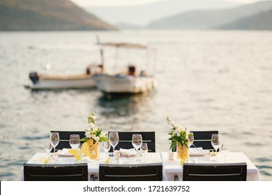 Wedding dinner table reception. Rectangular tables with white tablecloth, floral arrangements lemons in vases. Yellow paper butterflies are scattered on table. On beach, overlooking sunset at sea.