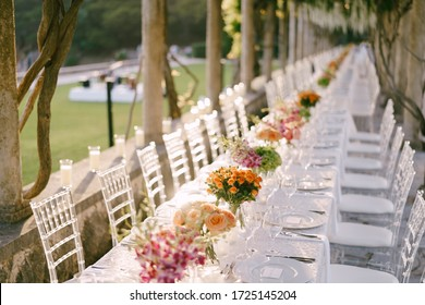 Wedding dinner table reception. A very long wedding table going into perspective. Bouquets of yellow, orange, pink roses on tables. Glass chairs Chiavari, Tiffany made of transparent plastic