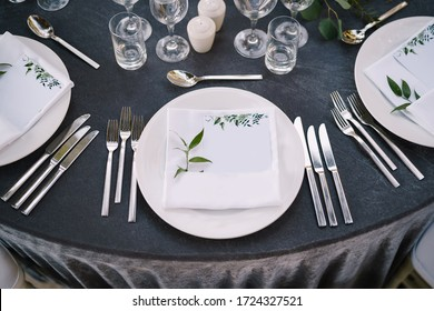 Wedding dinner table reception. White round plates on a round table with gray tablecloth, white Chiavari chairs with white pillows. A floral arrangement in the center of the table.