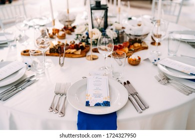 Wedding dinner table reception. White plate on the table, three forks on the left, three knives on the right. The wedding menu is in the plate. Top view