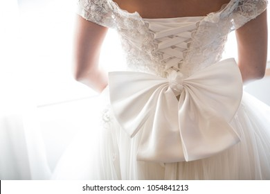 Wedding dress back detail. Close-up of brides beauty against white background