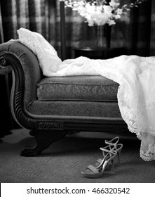 A wedding dress is carefully laid across the couch waiting for the bride with her shoes shown in the foreground.