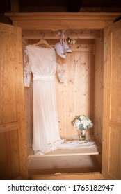 Wedding dress in the closet and a bouquet. - Shutterstock ID 1765182947