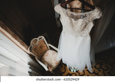 Wedding dress embroidered with crystals and pearls hangs over the chair