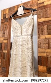 Wedding dress hanging against a mirror