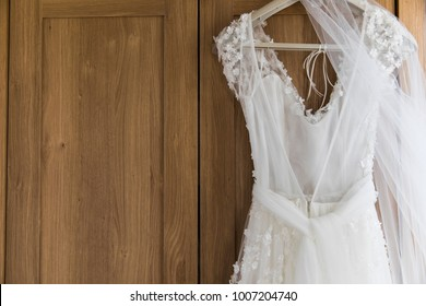 Wedding dress hanging against a wooden background