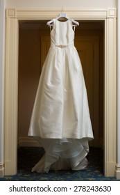 wedding dress hanging up by the door